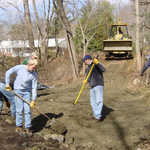At the Elm Street entrance to Synnott's Pond, Chris Mayer and Mike Feeney help prepare a path for heavy equipment.