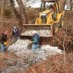 "Setting up stone ""baskets"" to prevent further storm-driven erosion at Synnott's Pond."