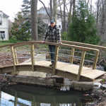 Senior Trailmaster Frank Eggert poses on the new bridge.