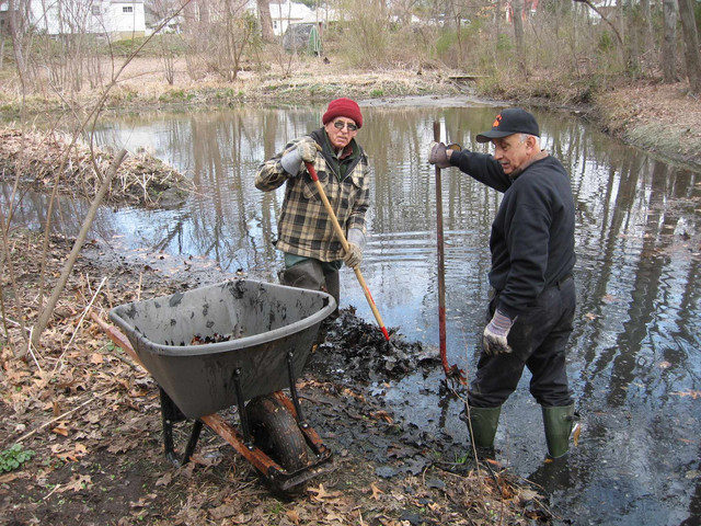 At the Spring Work Party, Frank Eggert and Bob Bevilacqua battle the never-ending accumulation of leaves and muck in Synnott's Pond.