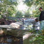 Derek Pedersen and daughter Casey watch as the pond banks are stabilized with heavy-duty fabric and plantings.